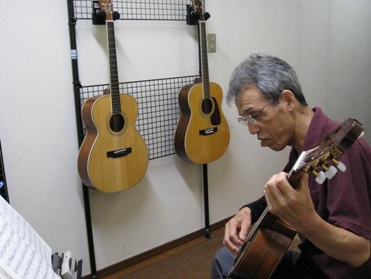 60代の男性がギターを弾く