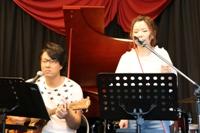先生のギター伴奏で歌う女性