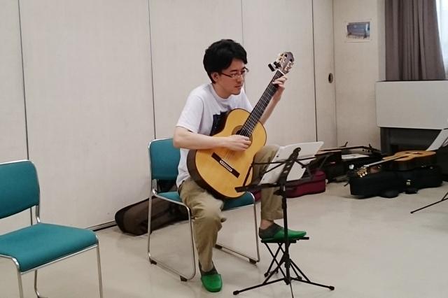 クラシックギターを弾く男性