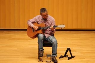60代の男性がアコースティックギターを弾く