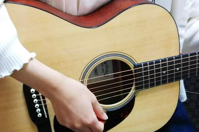 女性がアコースティックギターを弾く
