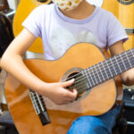 クラシックギタ-を弾く子供